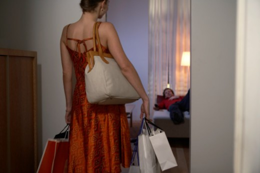 Woman carrying shopping entering room, man lying on bed in background : Stock Photo