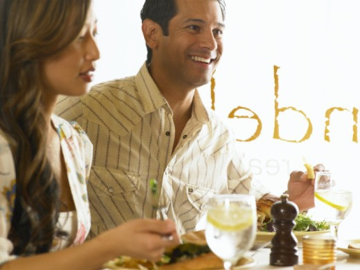 Man and woman eating meal in restaurant (focus on man smiling) : Stock Photo