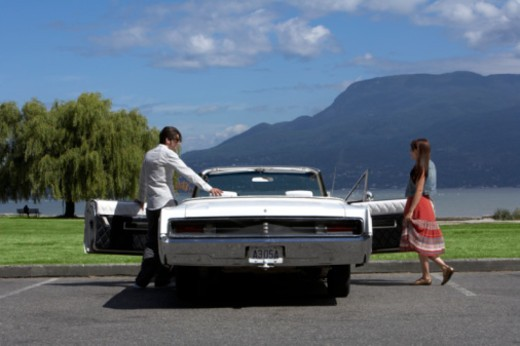 Stock Photo: 1598R-10047227 Couple climbing into white 60s convertible car, rear view