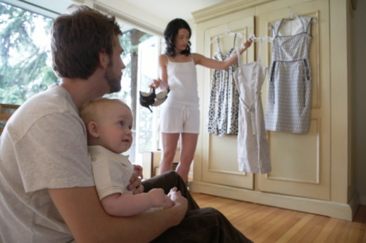 Woman dressing with husband and baby girl (6-9 months) in bedroom : Stock Photo
