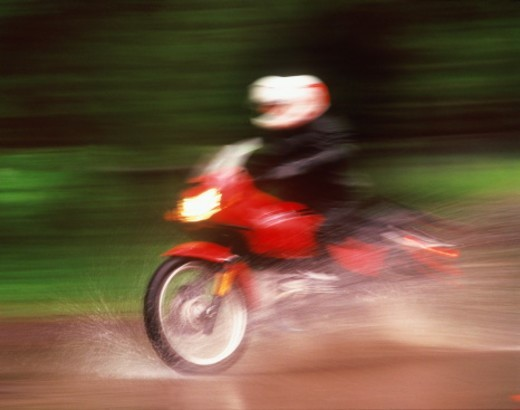 Motorcyclist on wet road (blurred motion) : Stock Photo