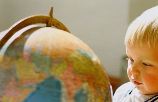 Baby (15-18 months) looking at globe, close-up : Stock Photo
