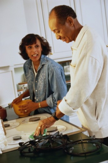 Stock Photo: 1598R-10048052 Mature couple cleaning kitchen