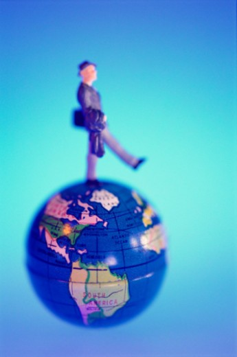 Businessman figurine walking on globe : Stock Photo