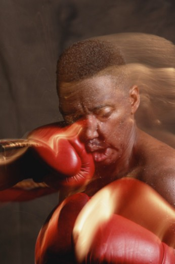 Stock Photo: 1598R-10050836 Boxer taking jab on face (blurred motion)