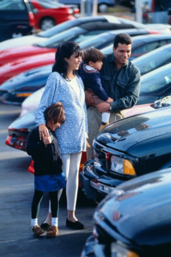 Family looking at cars at dealership : Stock Photo