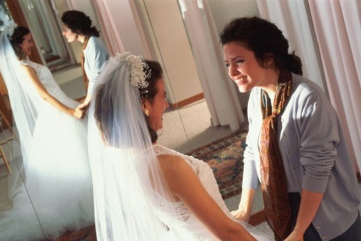Stock Photo: 1598R-10056085 Woman trying on wedding dress in  shop, holding hands with friend