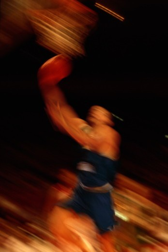 Basketball player jumping below basket (blurred motion) : Stock Photo