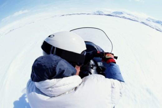 Person driving snowmobile, rear view (wide angle) : Stock Photo