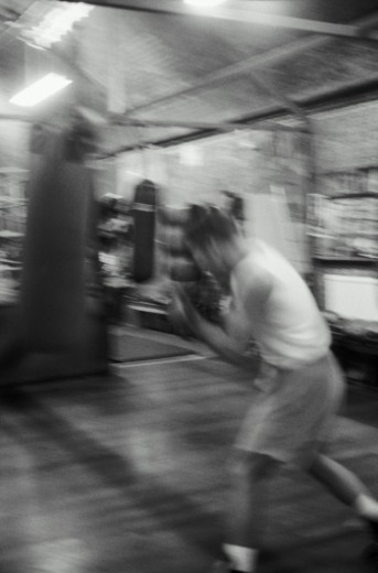 Stock Photo: 1598R-10057388 Boxer training on heavy bag in gym (blurred motion, B&W)