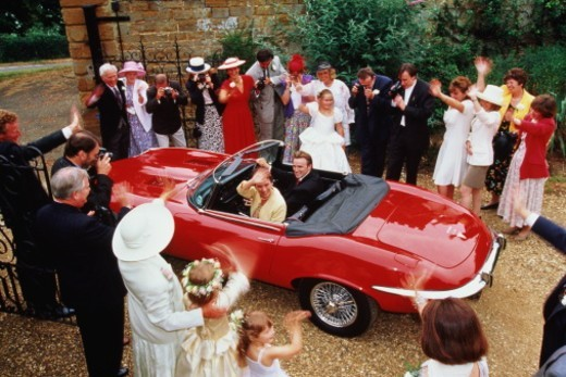 Bride and groom in red sports car, waving goodbye to guests : Stock Photo