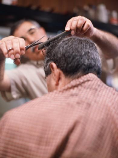 Stock Photo: 1598R-10058344 Barber cutting mature man's hair, close-up