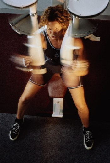 Stock Photo: 1598R-10058370 Young woman using exercise machine, blurred movement,high angle view