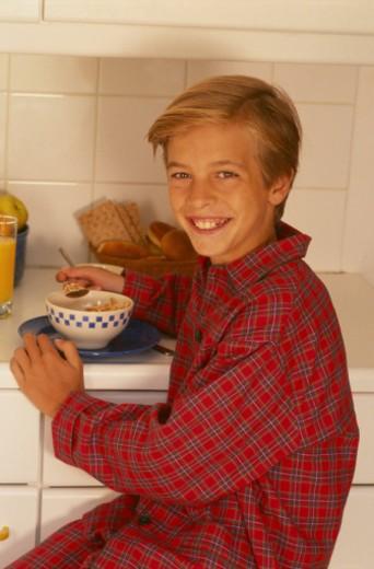 Stock Photo: 1598R-100604 Boy (8-9) eating breakfast