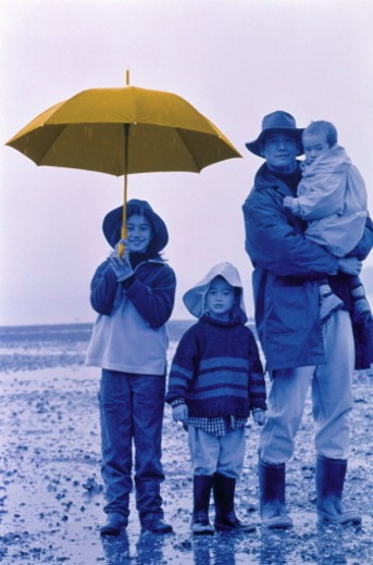Father standing with children in rain (B&W, Hand Tinted) : Stock Photo