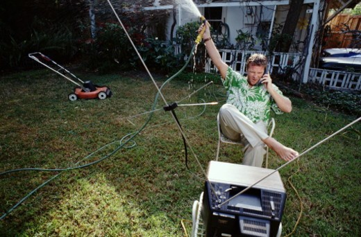 Man sitting in backyard watching T.V, talking on phone and watering : Stock Photo