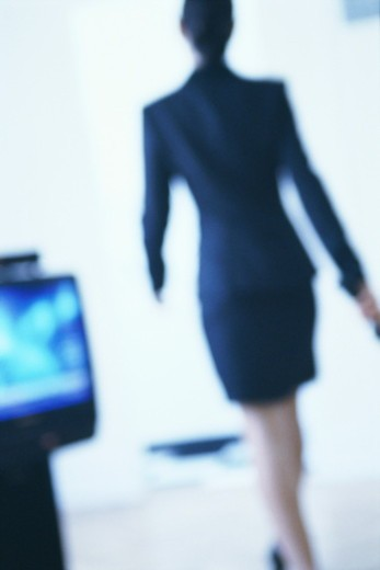 Woman walking in room, rear view (defocussed) : Stock Photo