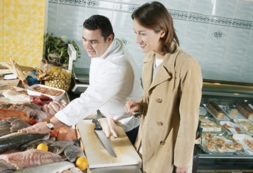 Chef explaining about seafood to woman in kitchen counter : Stock Photo