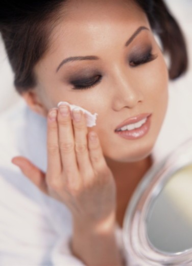 Young woman applying cream to face, close-up : Stock Photo