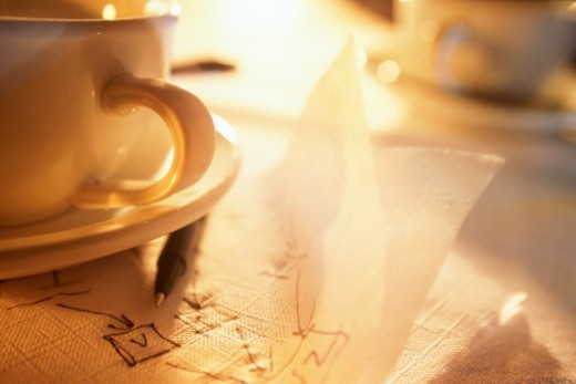 Notes scribbled on napkin beside cups and saucers, close-up : Stock Photo