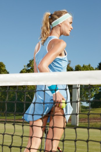 Young female tennis player standing behind the net lifting backside of skirt while looking off to the right. : Stock Photo
