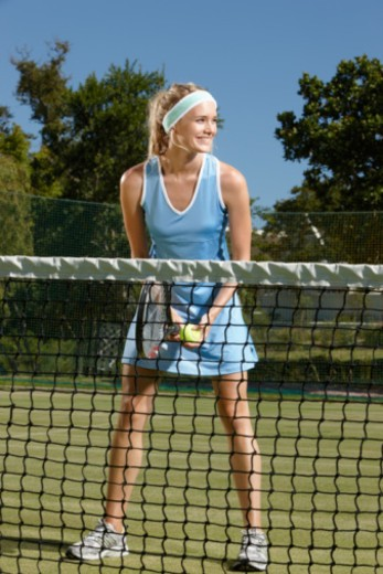 Stock Photo: 1598R-10067148 Young female tennis player standing on court smiling.