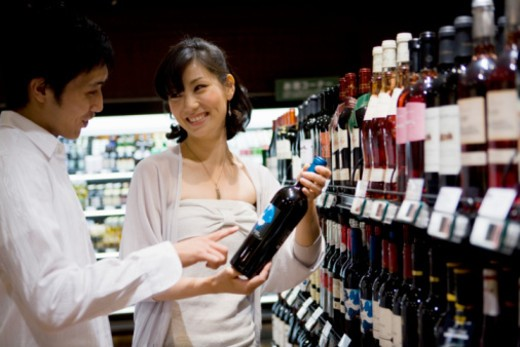 Stock Photo: 1598R-10067385 Young couple chooses wine in shop