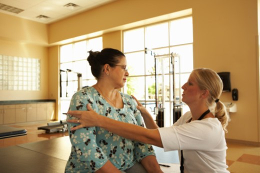 Stock Photo: 1598R-10067662 Mature woman working with therapist in therapy gym designed to rehabilitate patients recovering from physical and neurological injury