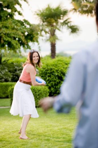 Woman throwing plastic disc : Stock Photo