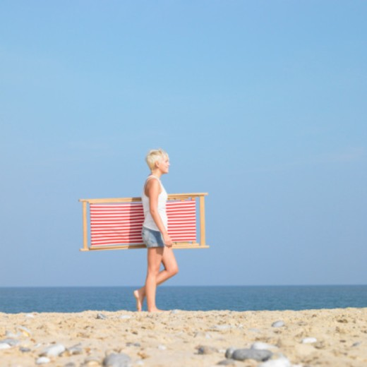 Stock Photo: 1598R-10067733 Young woman walking along beach with deck chair.