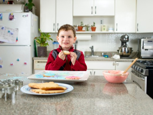 Boy eating a frosted cookie : Stock Photo