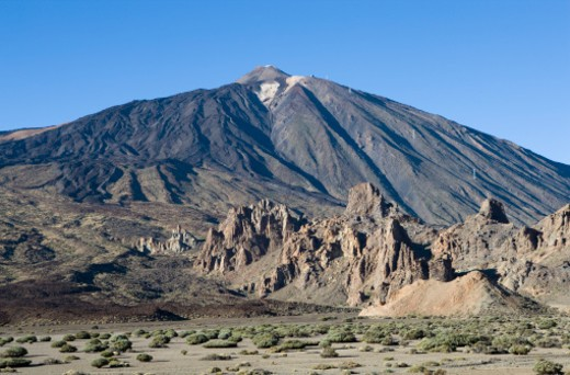 the volcano Mount Teide dominates the centre of the island of Tenerife with Los Roques de Garcia in the foreground : Stock Photo