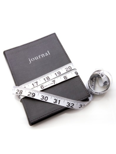 Stock Photo: 1598R-10068040 Measuring tape wrapped around personal weight journal
