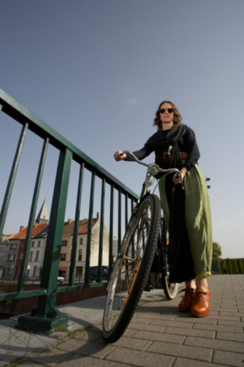 fashionable lady standing next to a railing overlooking canal a day in the life of : Stock Photo