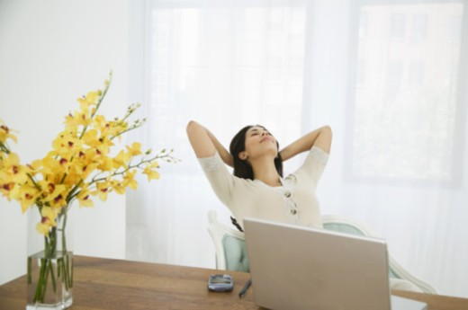 Hispanic woman kicking back by computer, resting head on folded arms, feeling of accomplishment : Stock Photo