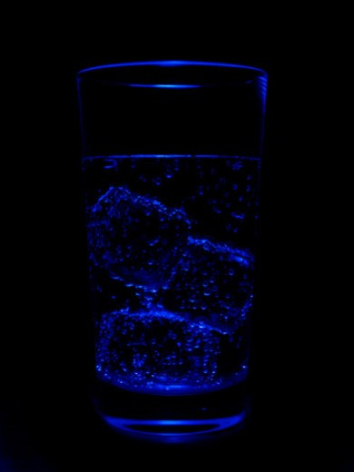 Blue glimmering ice cubes and water glass : Stock Photo
