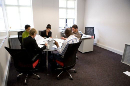 Five men and women meeting around a table in an office building : Stock Photo