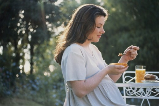 Pregnant woman eating papaya, muffin, and orange juice : Stock Photo