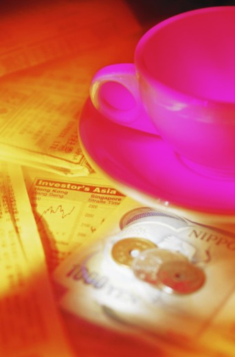 Japanese banknote, coins and cup on investor's guide (gel effect) : Stock Photo