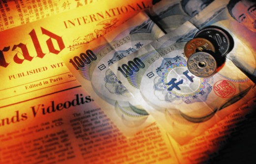 Stock Photo: 1598R-10070404 Japanese banknotes and coins on newspaper, close-up (gel effect)
