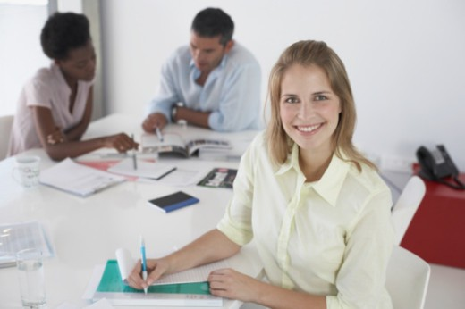 Portrait of business woman in office, two colleagues in background : Stock Photo