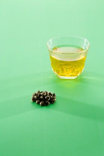 Glass of chinese tea and tea leaves : Stock Photo