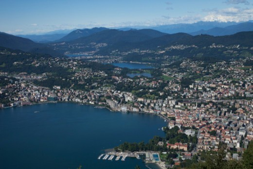 Lake Lugano is a glacial lake in the south-east of Switzerland, at the border between Switzerland and Italy. The lake, named after the city of Lugano, is situated between Lake Como and Lago Maggiore. : Stock Photo