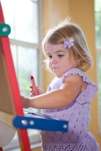Baby drawing on easel : Stock Photo