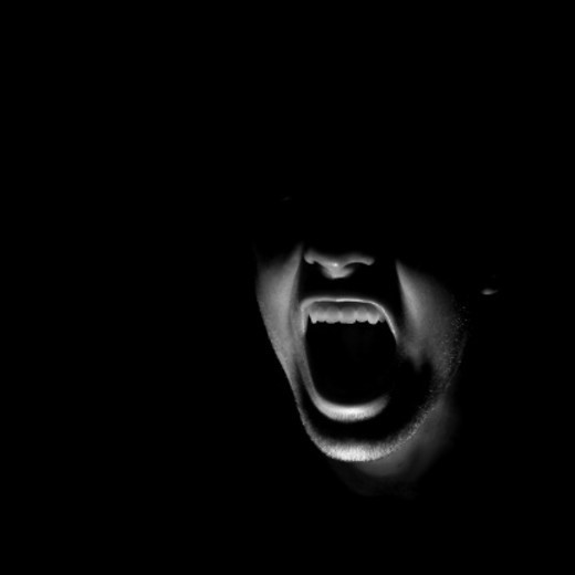 Male face screaming in darkness : Stock Photo