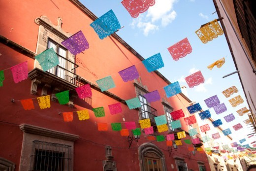 North America, Mexico, San Miguel de Allende, streamers of tissue paper flags hang between colonial buildings during Day of the Dead celebrations. Flags are known as 'Papel Picado' : Stock Photo