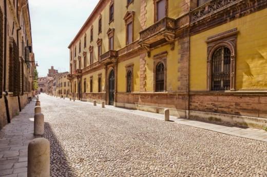 Street is Corso Ercole I d'Este with Castello Estense at far end.  Palazzo Canonici Mattei at right (Neo-Renaissance style). : Stock Photo