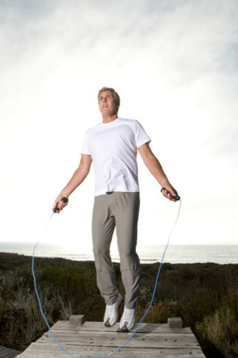 Mature man skipping rope on jetty : Stock Photo