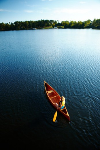 Red canoe paddling on lake : Stock Photo