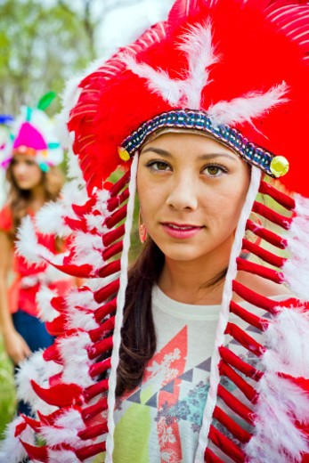 Two girlfriends wearing native american headdresses outside in a park. : Stock Photo
